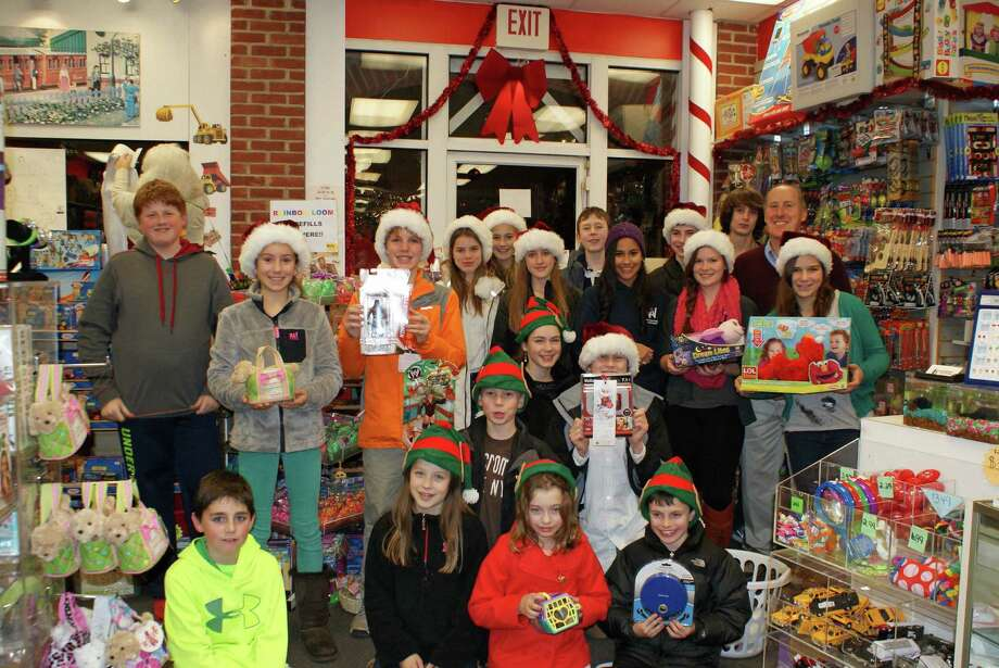 New Canaan Toy Store owner Chris Kilbane joins members of the First Presbyterian Churchís middle school and high school youth groups, who shopped for the Salvation Armyís gift-giving program at the New Canaan Toy Store in December. Photo: Contributed Photo, Contributed / New Canaan News Contributed