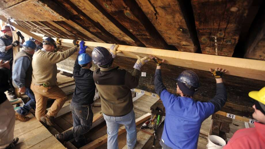 Shipwrights and other workers at the Mystic Seaport's H.B. DuPont Preservation Shipyard in Stonington, Conn.work install the first of the new hull planks on the whale ship Charles W. Morgan Tuesday, Feb. 21, 2012. The 36-foot long, 14-inch wide and 4-inch thick longleaf yellow pine plank was milled in the shipyard and steamed for 3-hours to soften it before being installed. Shipwrights expect to install a new plank every few days for some time before stepping-up the process until the hull is fully sheathed. The $7 million project is on schedule to re-launch her on July 21, 2013, the 172nd anniversary of her first trip down the ways in 1841. Mystic Seaport will return the Morgan to sea for a ceremonial 38th Voyage to historic ports on the East Coast in the late spring and summer of 2014. (AP Photo/The Day, Sean D. Elliot) MANDATORY CREDIT Photo: SEAN D. ELLIOT, Associated Press