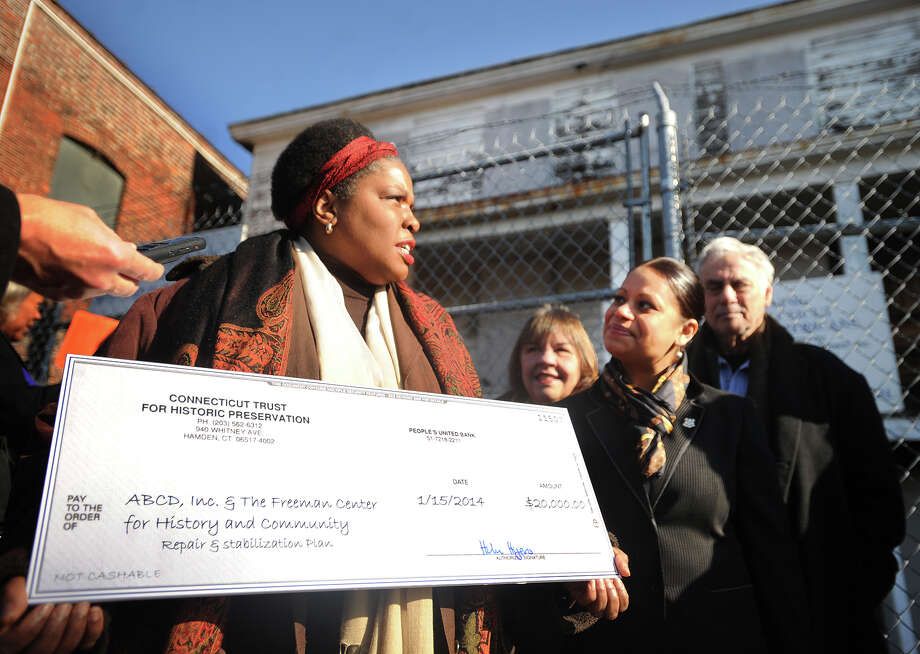 Maisa Tisdale, president/CEO of The Mary & Eliza Freeman Center for History and Community, holds a 20 thousand dollar check from the Connecticut Trust for Historic Preservation during a ceremony outside the Mary and Eliza Freeman houses, the oldest dwellings in Connecticut constructed by African Americans, on Main Street in BRidgeport's South End on Wednesday, January 15, 2014. At right is State Rep. Christina Ayala. Photo: Brian A. Pounds / Connecticut Post