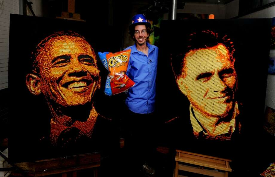 Artist Jason Baalman poses in front of portraits of President Barack Obama and former Gov. Mitt Romney made entirely of more than 2,000 individual Cheetos snacks Tuesday, Oct. 2, 2012, in Baalman's Colorado Springs, Colo., studio.  Today, the Cheetos brand unveiled a new electoral polling model with the unveiling of 3 feet by 4 feet one-of-a-kind Cheetos portraits of the Democratic and Republican presidential nominees – President Barack Obama and former Gov. Mitt Romney. Photo: Jack Dempsey, Associated Press