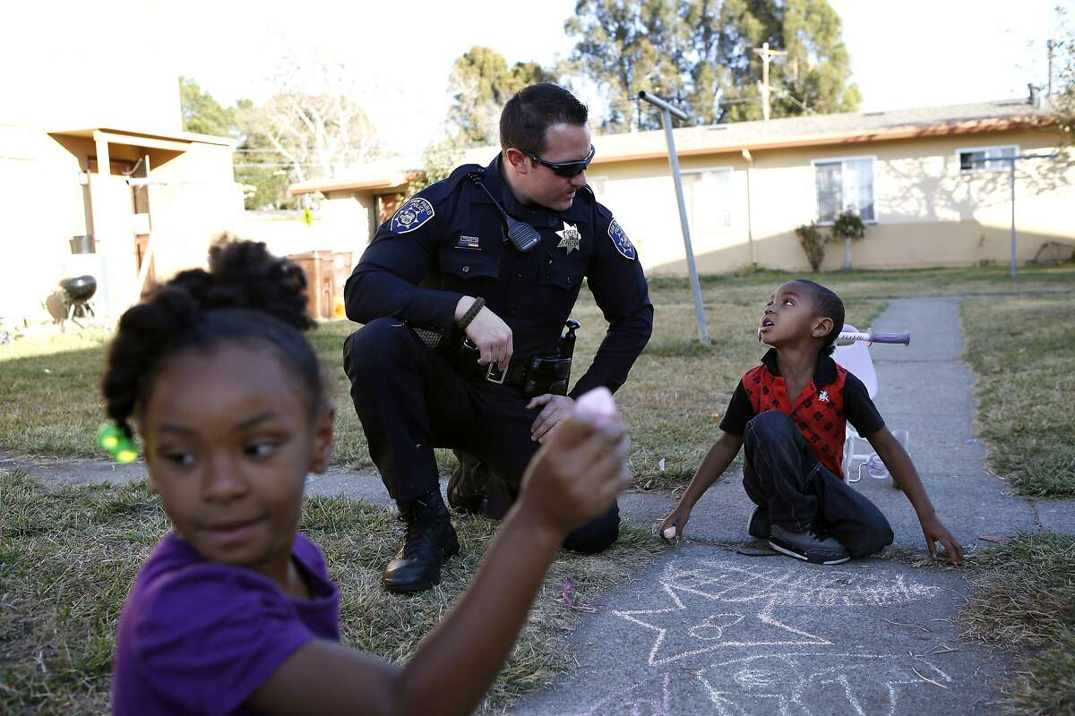 While on foot patrol, Officer Carducci talks with Jayon Evans, 4, while he and his sister Jayonia Evans, 5, draw with chalk on the sidewalk in the San Pablo Housing Projects in San Pablo, CA, Tuesday, January 14, 2014. San Pablo, CA, with a population of 30,000, had zero homicides last year, due in part to the police taking a more active role in the community with increased foot patrols, interactions with citizens and youth programs.