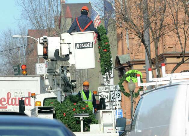 Workers take down Christmas wreaths from light posts along Broadway on Wednesday, Jan. 15, 2014 in Saratoga Springs, N.Y.  (Lori Van Buren / Times Union) Photo: Lori Van Buren