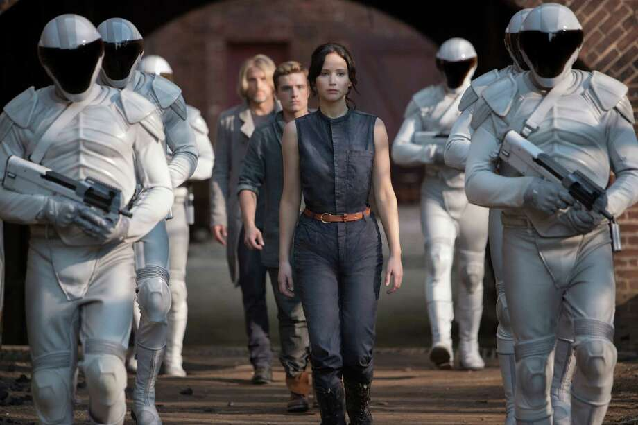"This image released by Lionsgate shows Jennifer Lawrence as Katniss Everdeen, from foreground to background, Josh Hutcherson as Peeta Mellark and Woody Harrelson as Haymitch Abernathy in a scene from ""The Hunger Games: Catching Fire."" (AP Photo/Lionsgate, Murray Close) ORG XMIT: NYET536 Photo: Murray Close / Lionsgate"