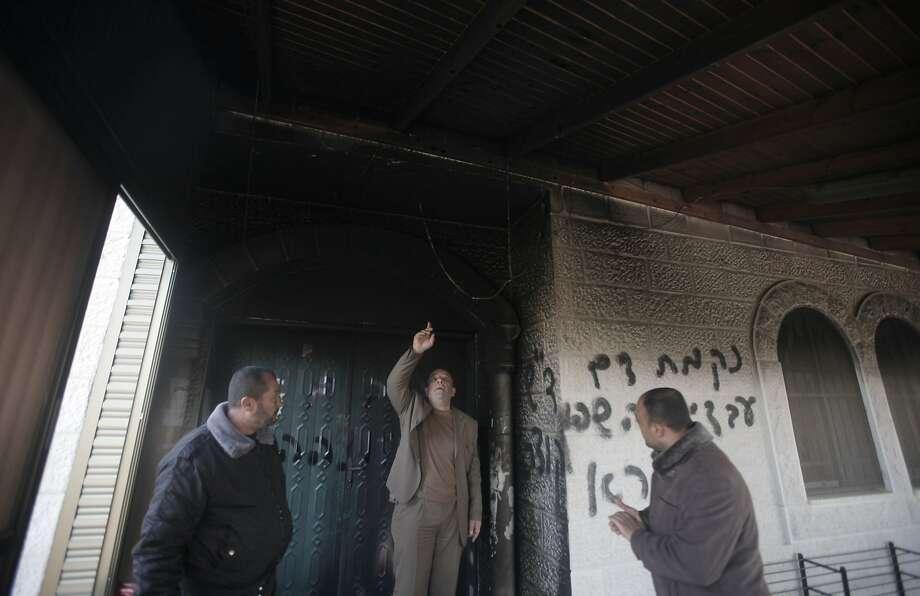 "Palestinians inspect the entrance to of a mosque scrawled with graffiti that reads in Hebrew, ""Arabs out"" and ""Revenge for blood spilled in Qusra"" in the West Bank village of Deir Istiya which lies next to the sprawling Ariel settlement in the northern Israeli occupied West Bank, on January 15, 2014. Suspected Jewish extremists torched the entrance to the mosque in an apparent revenge attack for Palestinians beating and detaining Israeli settlers last week who were later arrested on suspicion of provoking the violence when they entered Qusra from Esh Kodesh, an illegal settlement outpost nearby. AFP PHOTO/JAAFAR ASHTIYEHJAAFAR ASHTIYEH/AFP/Getty Images Photo: Jaafar Ashtiyeh, AFP/Getty Images"