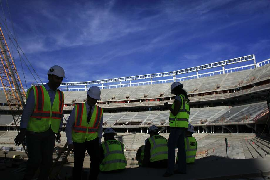 Construction workers and members of the press walk around the Levi's Stadium construction site after the first seats were installed on Tuesday Oct. 1, 2013 in Santa Clara, Calif. The new stadium will hold 68,500 fans during home games. Photo: Mike Kepka, The Chronicle