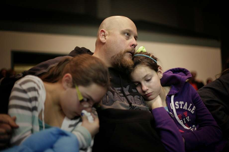 Troy Tucker holds daughters Emily, 10, (left) and Hannah, 12, during a prayer vigil for the victims of the Berrendo Middle School shooting in Roswell, N.M. Photo: Pat Vasquez-Cunningham, Associated Press