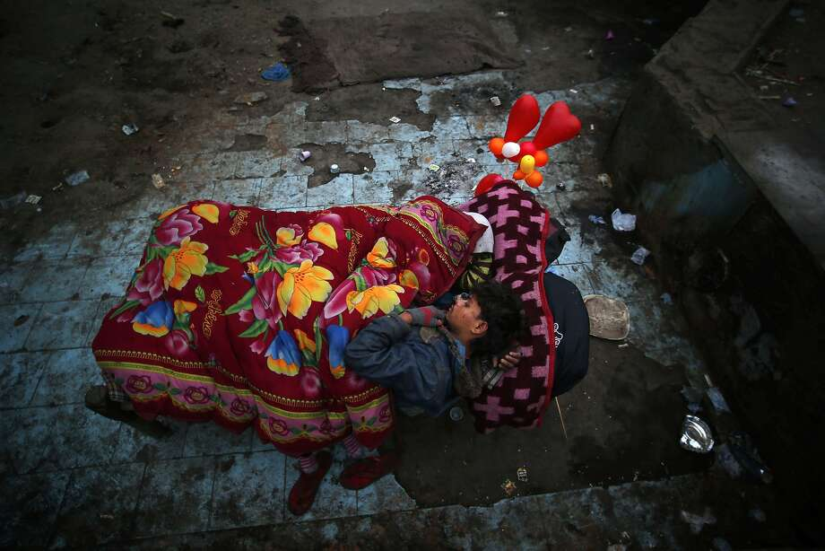 Bed, no breakfast: A homeless man and his wife (white scarf) share a rented bed adorned with heart-shaped balloons in a poor neighborhood of New Delhi. A bed on a cot with blankets costs approximately $.50 per night. A bed without the cot is $.15. Photo: Saurabh Das, Associated Press
