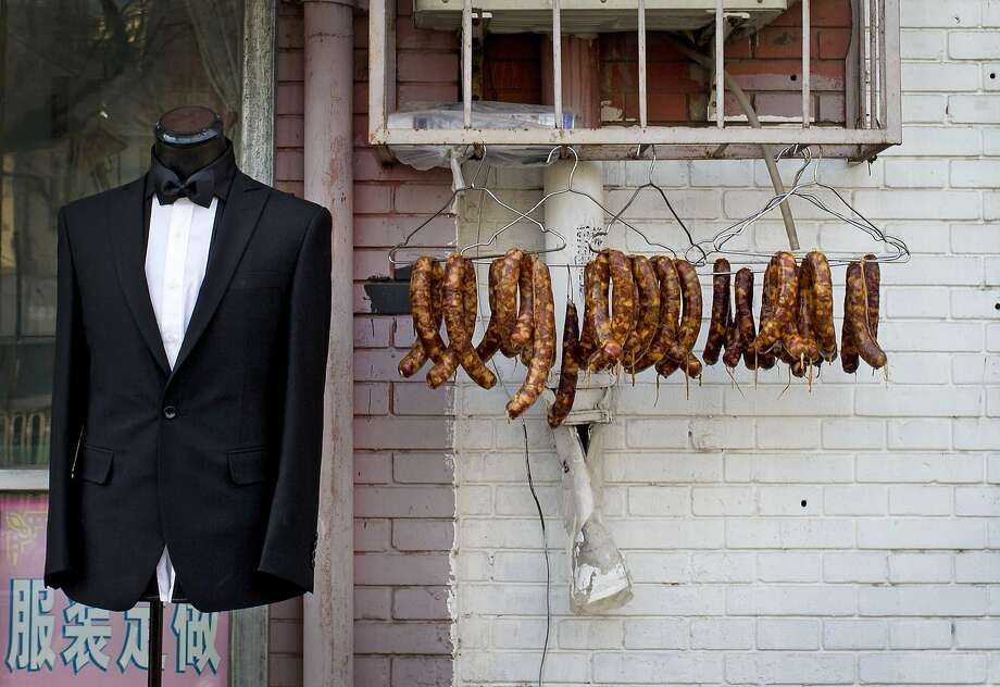 Let us fit you in a classy casing: A tailor shop in Beijing hangs out sausages to attract clothes hounds. Photo: Andy Wong, Associated Press