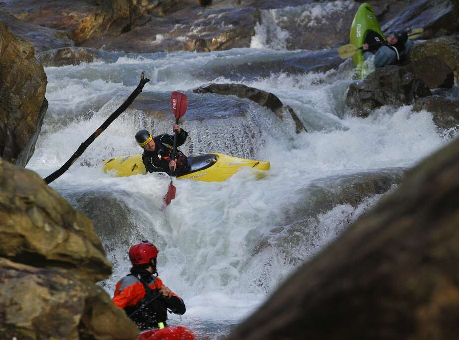 "Up the Suck with a paddle:Garrett Mays looks at Bett Adams (center) and Luke Scott running the ""Road Construction"" rapid while kayaking on Suck Creek in Marion County, Tenn. Scott appears to be detoured by a couple of boulders. Photo: Dan Henry, Associated Press"