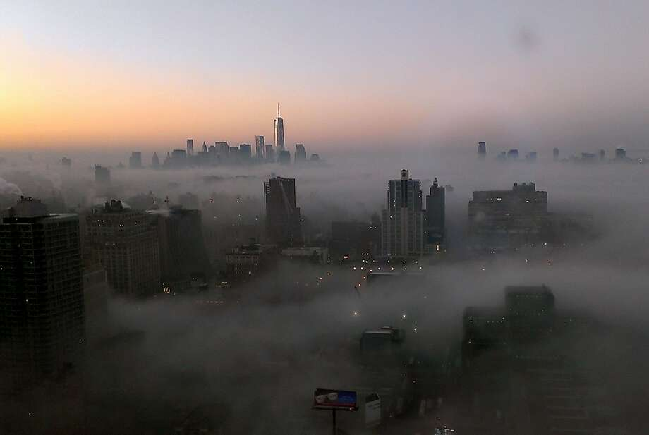 The tower of New York's World Trade Center rises through a blanket of fog on Wednesday morning, Jan. 15, 2014, in this view looking south from the 48th floor at 42nd Street and 11th Avenue in Midtown Manhattan. New Jersey is visible at top right. (AP Photo/Girish Tewani) Photo: Girish Tewani, Associated Press