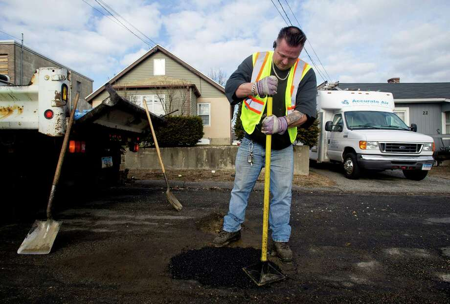 David Plunkett fills a pothole on Larkin Street in Stamford, Conn., with cold patch on Wednesday, January 15, 2014. Photo: Lindsay Perry / Stamford Advocate