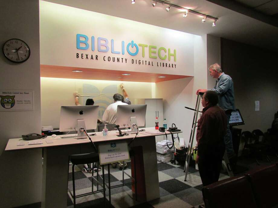 Bexar County employees put the final touches on the BiblioTech branch in the central jury room. Two employees will staff the counter, where county residents can register for a BiblioTech account and check out one of 200 electronic reading devices. There is also a kiosk on-site, where BiblioTech account holders can check out books. Photo: Eva Ruth Moravec, San Antonio Express-News / San Antonio Express-News