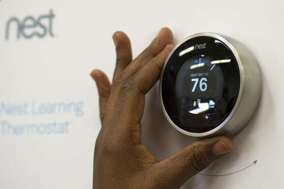 A customer checks a Nest Labs Inc. digital thermostat on display at a Home Depot Inc. store in Emeryville, California, U.S., on Tuesday, Jan. 14, 2014. Google Inc., after struggling to catch Apple Inc. in consumer gadgets, is buying Nest Labs Inc., the digital thermostat maker for $3.2 billion in cash. Photographer: David Paul Morris/Bloomberg