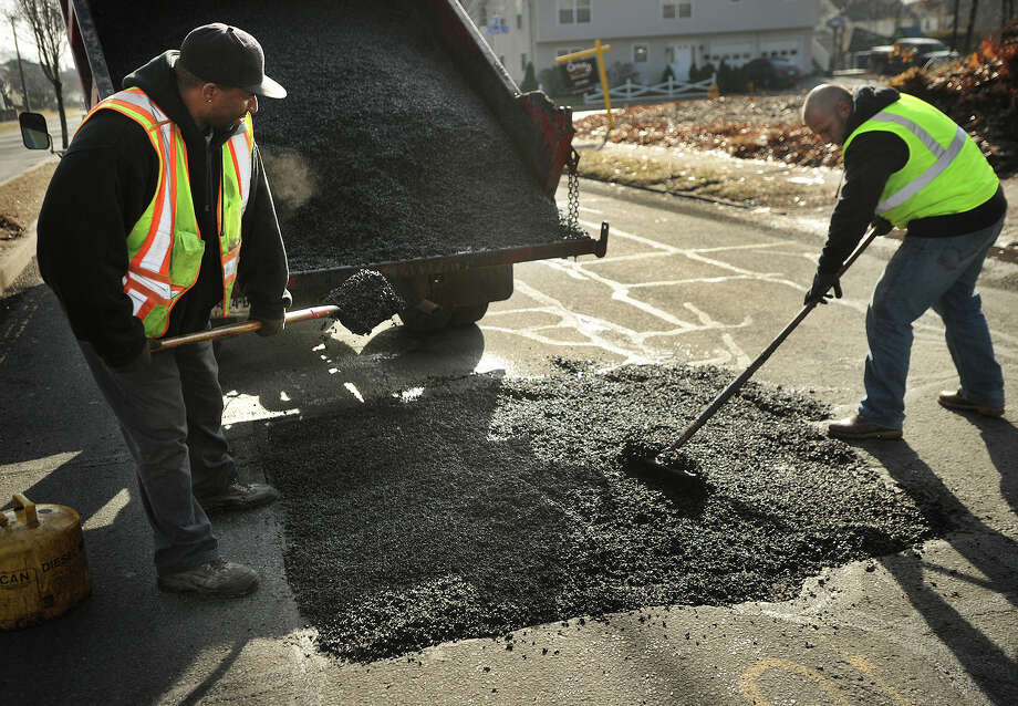 City workers Les Randolph, left, and Daniel Docu, use cold patch to fill in a large pothole caused by a sunken utility company patch on Main Street in Bridgeport, Conn. on Wednesday, January 15, 2014. Photo: Brian A. Pounds / Connecticut Post