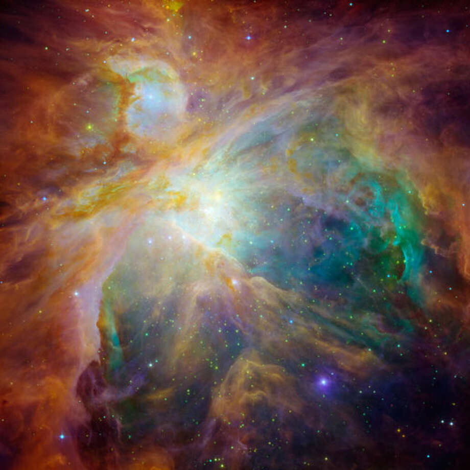 """Now for some earlier image of OrionNASA's Spitzer and Hubble Space Telescopes teamed up to expose the chaos that baby stars are creating 1,500 light years away in a cosmic cloud called the Orion nebula. This striking composite indicates that four monstrously massive stars, collectively called the """"Trapezium,"""" at the center of the cloud may be the main culprits in the Orion constellation, a familiar sight in the fall and winter night sky in the northern hemisphere. Their community can be identified as the yellow smudge near the center of the image.Swirls of green in Hubble's ultraviolet and visible-light view reveal hydrogen and sulfur gas that have been heated and ionized by intense ultraviolet radiation from the Trapezium's stars. Meanwhile, Spitzer's infrared view exposes carbon-rich molecules called polycyclic aromatic hydrocarbons in the cloud. These organic molecules have been illuminated by the Trapezium's stars, and are shown in the composite as wisps of red and orange. On Earth, polycyclic aromatic hydrocarbons are found on burnt toast and in automobile exhaust.Stellar winds from clusters of newborn stars scattered throughout the cloud etched all of the well-defined ridges and cavities in Orion. The large cavity near the right of the image was most likely carved by winds from the Trapezium's stars. Located 1,500 light-years away from Earth, the Orion nebula is the brightest spot in the sword of the Orion, or the """"Hunter"""" constellation. The cosmic cloud is also our closest massive star-formation factory, and astronomers believe it contains more than 1,000 young stars.Image credit: NASA/JPL-Caltech/STScI"""