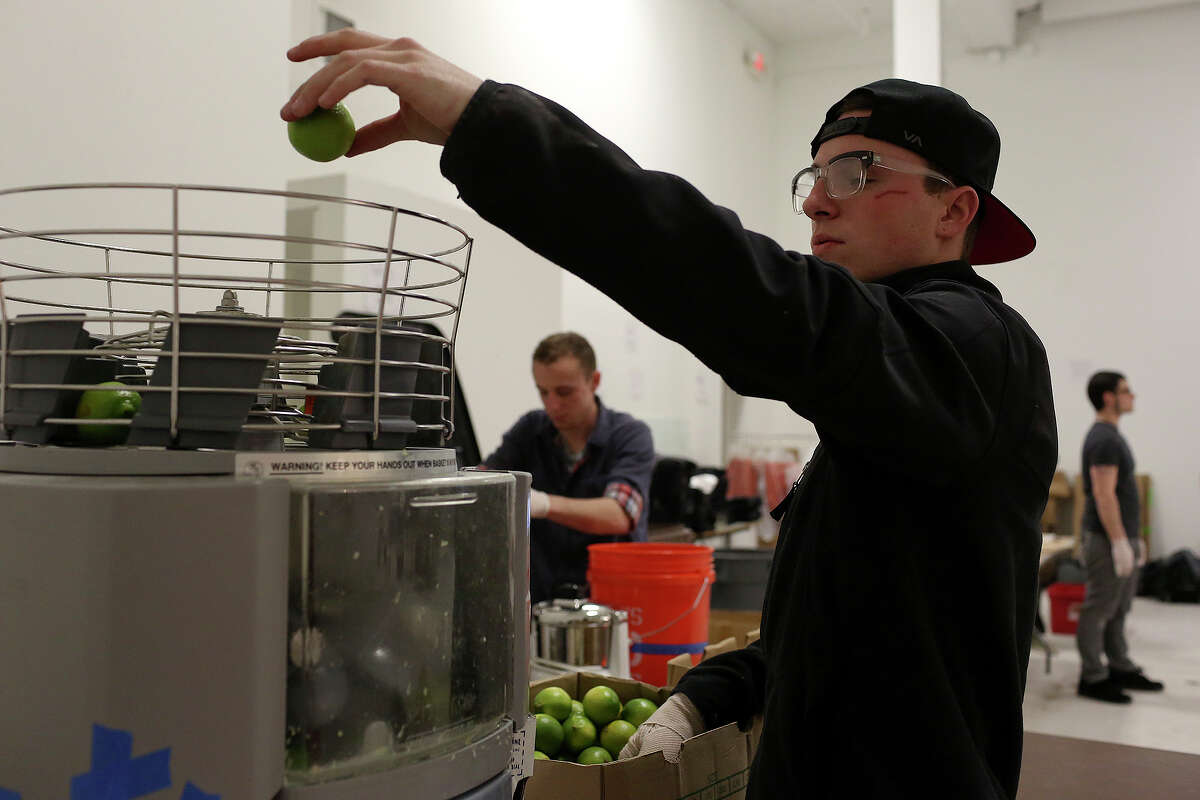 Patrick Hack juices limes in preparation for this weekend's San Antonio Cocktail Conference on Tuesday, Jan. 14, 2014. Patrick is a server assistant at Bohanan's.