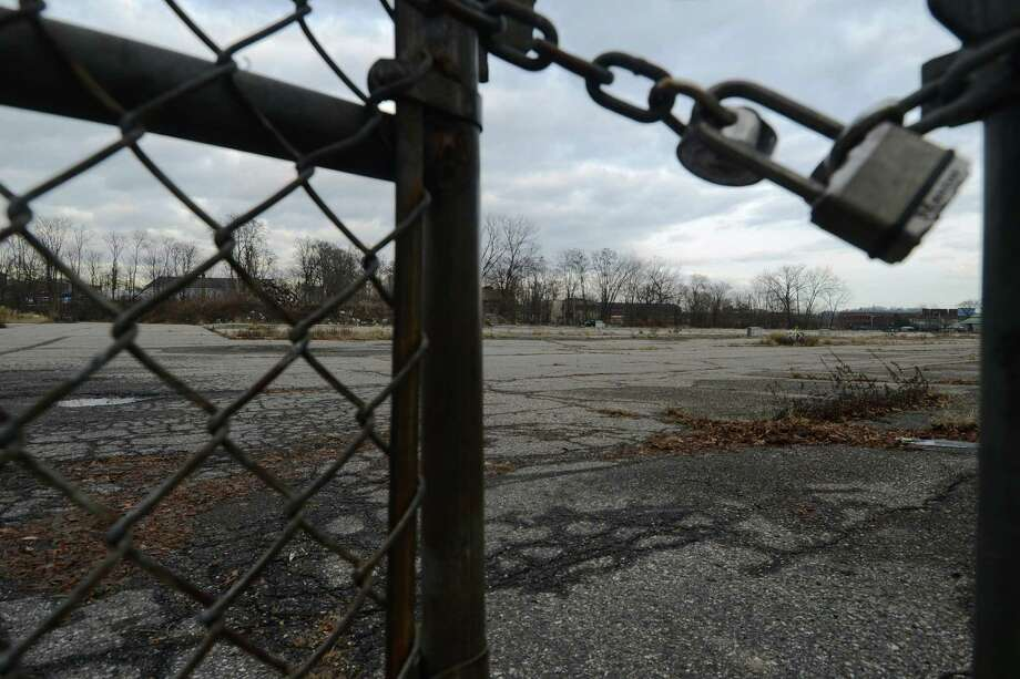 A lock keeps trespassers out of the abandoned Kennedy Place in Danbury, Conn. on Wednesday, Jan. 15, 2014.  A developer just got a tax break to build 367 apartments in the vacant lot. Photo: Tyler Sizemore / The News-Times