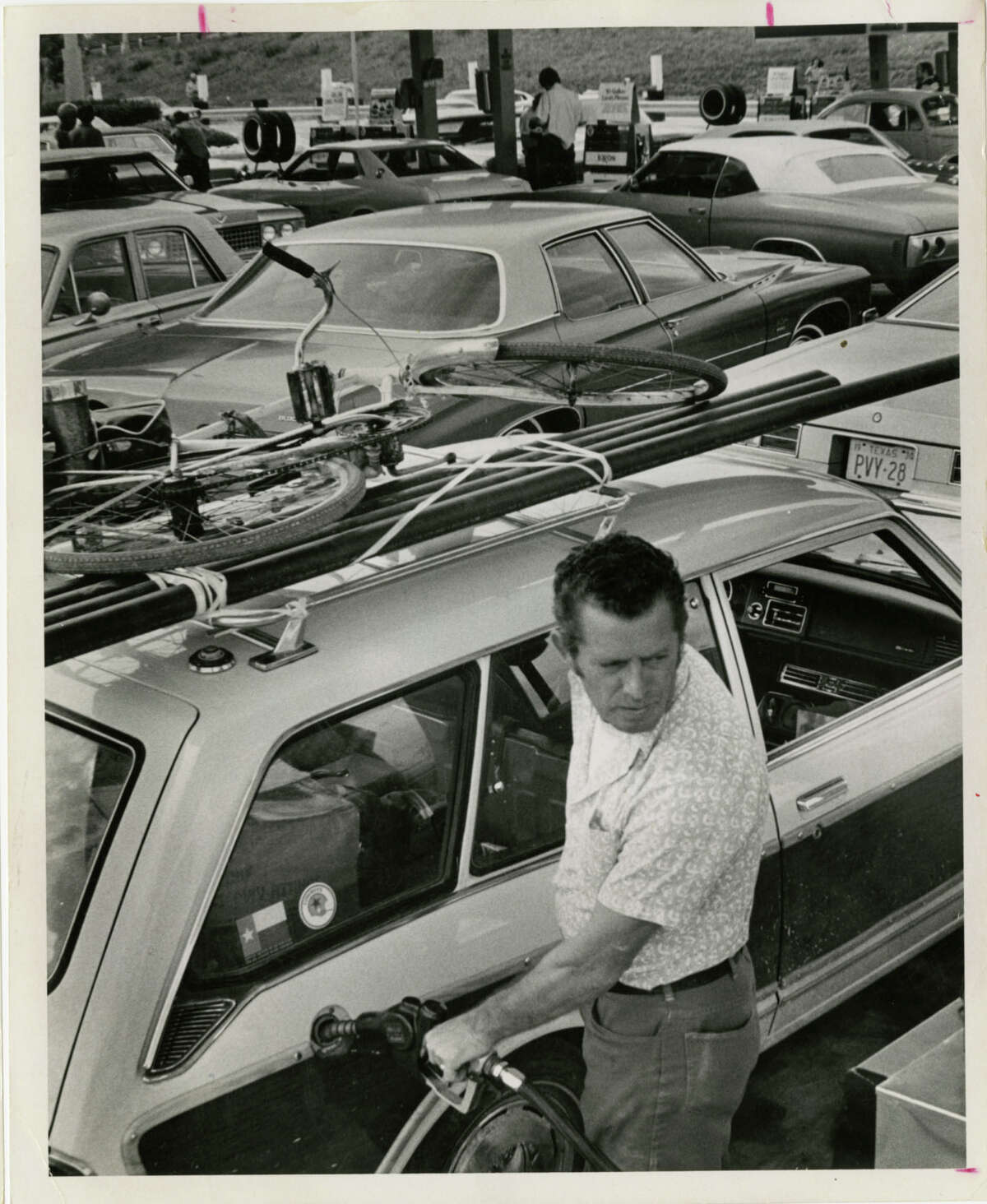 03/01/1974 - Alfred Wilson fills up his car in a crowded Exxon service station at Newcastle and the Southwest Freeway. The station opened their pumps at 3:00 pm today. Wilson drives around with a bicycle on top of his car in case he runs out of gas and has to cycle to a service station.