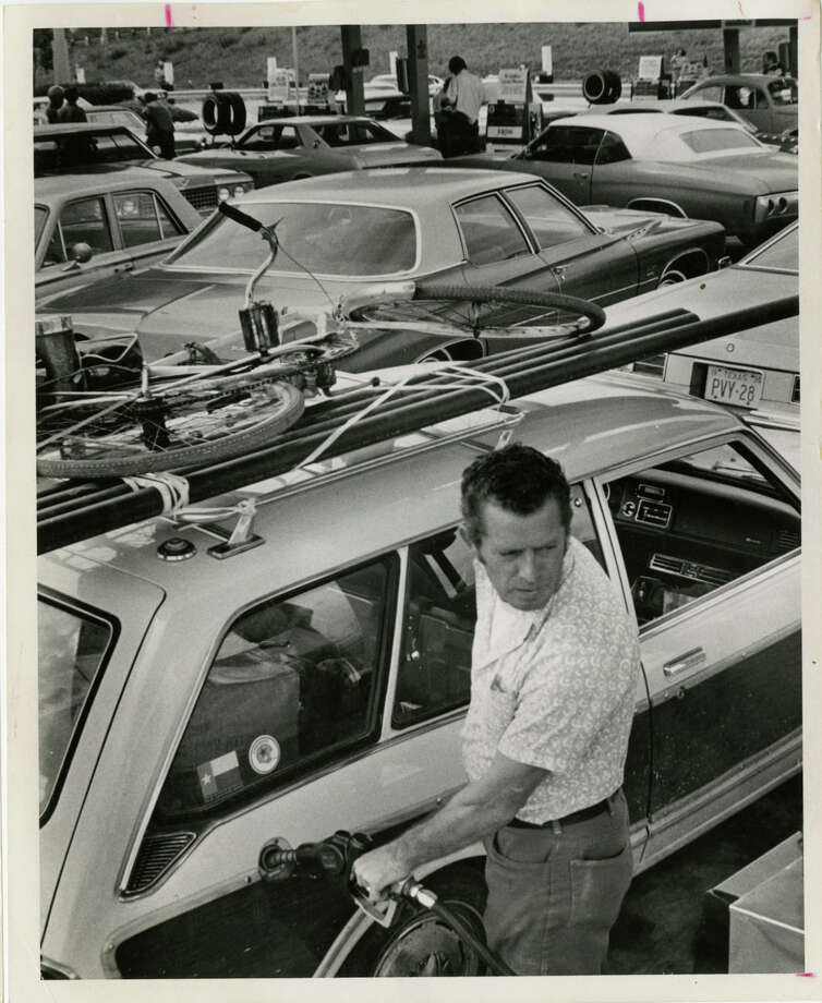 03/01/1974 - Alfred Wilson fills up his car in a crowded Exxon service station at Newcastle and the Southwest Freeway. The station opened their pumps at 3:00 pm today. Wilson drives around with a bicycle on top of his car in case he runs out of gas and has to cycle to a service station. Photo: Bela Ugrin, HP Staff / Houston Post files
