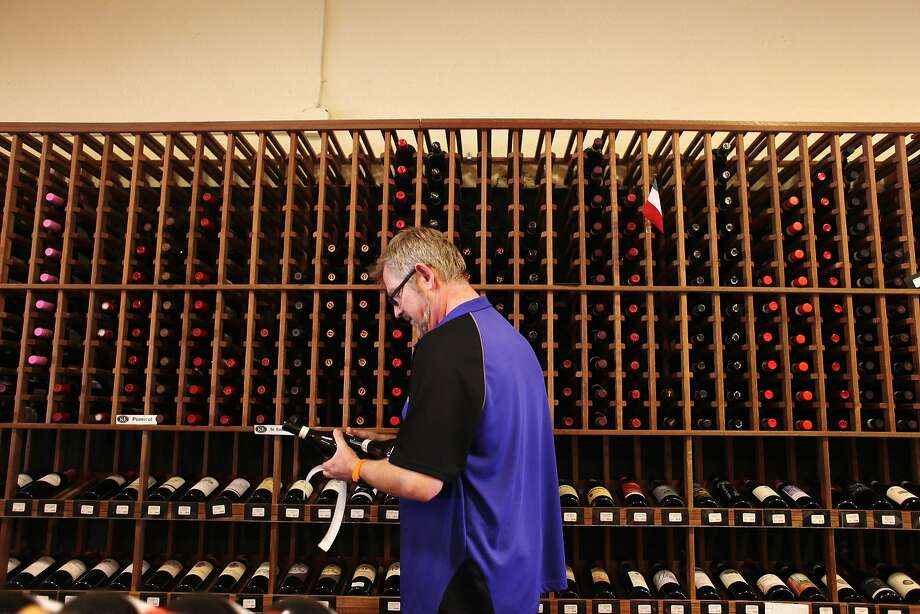 "Mike ""Guido"" Parres, an Italian wine specialist, restocks bottles of wine in October at K&L Wine Merchants on Fourth Street in San Francisco. The United States has become the largest wine-buying country in the world. Photo: Pete Kiehart, The Chronicle"