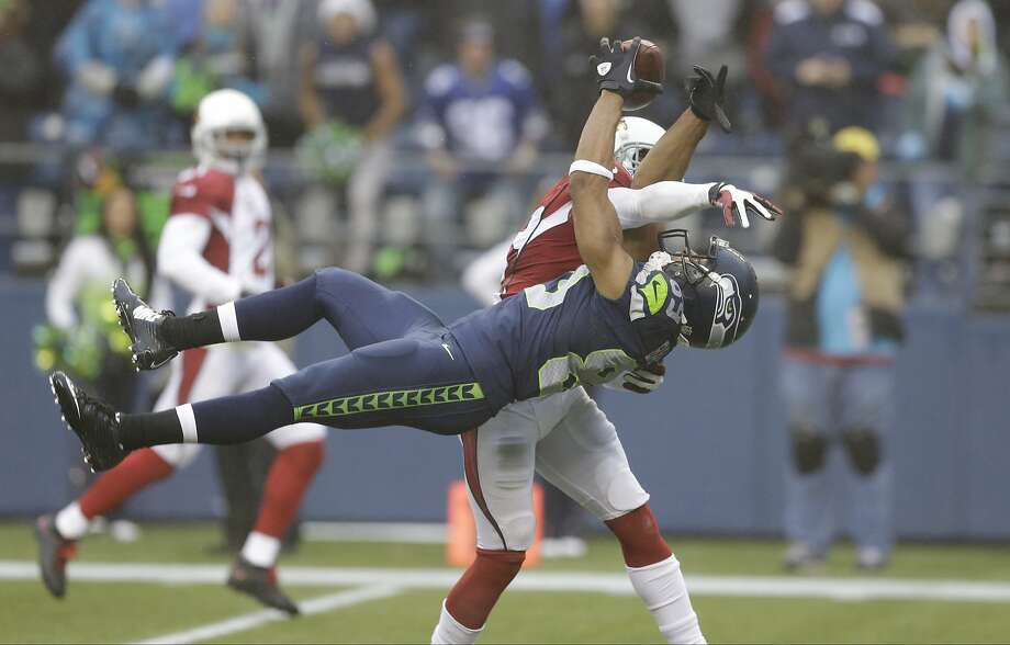 Arizona Cardinals cornerback Jerraud Powers, back, breaks up a pass intended for Seattle Seahawks wide receiver Doug Baldwin in the second half of an NFL football game, Sunday, Dec. 22, 2013, in Seattle. (AP Photo/Elaine Thompson) Photo: Elaine Thompson, Associated Press
