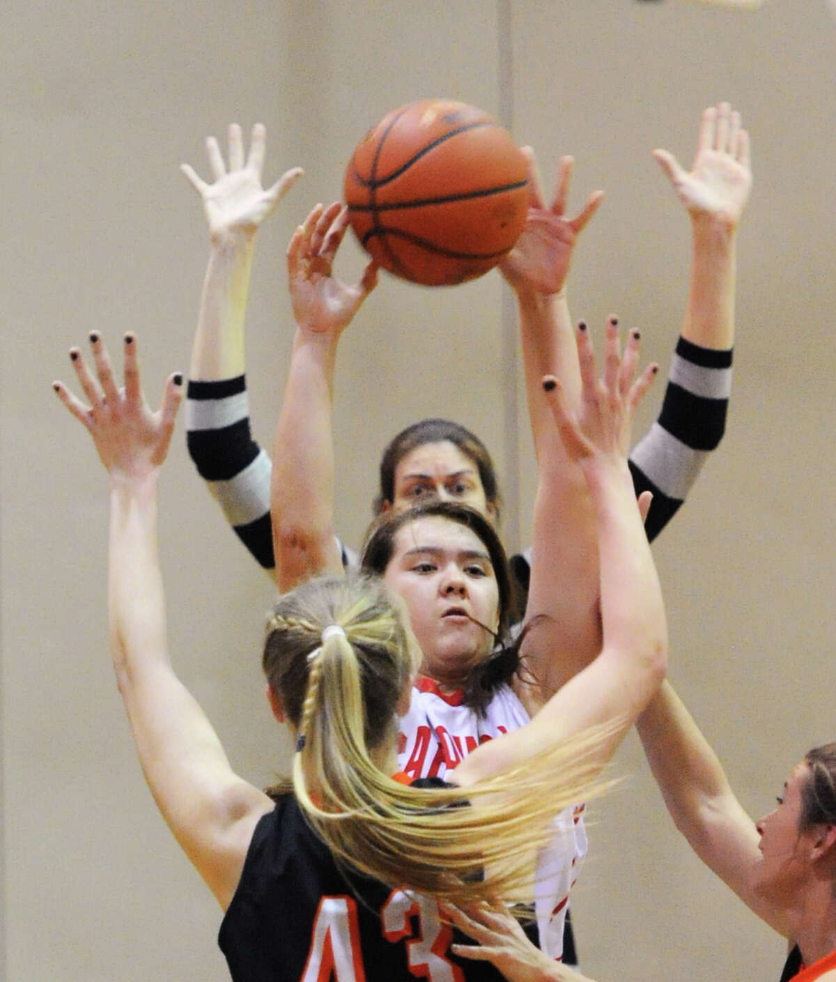 As Ridgefield High School Girls Basketball Coach, Katie Reed, background, signals for her defender, Kaitlyn Kynast (#43), foreground, to keep her hands up, Jamie Kockenmeister, center, of Greenwich, passes the ball during the game between Greenwich High School and Ridgefield High School at Greenwich, Tuesday night, Jan. 14, 2014.