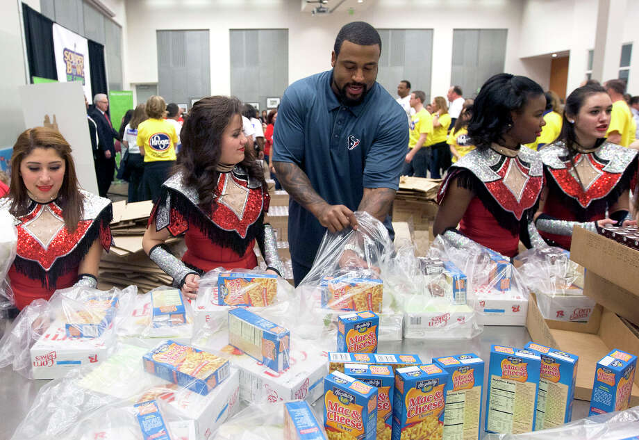 Houston Texans offensive tackle Duane Brown helps package donated goods during the kickoff of the Souper Bowl of Caring Houston 2014 at the Houston Food Bank, Wednesday, Jan. 15, 2014, in Houston. The Houston campaign is the largest one in the nation, with a 2014 goal of generating enough food and money to provide 2.8 million meals to hungry neighbors in Houston. The campaign is a nationwide, grassroots movement of caring utilizing the energy of the Super Bowl to mobilize youth to fight hunger and poverty in their local communities. Photo: Cody Duty, Houston Chronicle / © 2014 Houston Chronicle