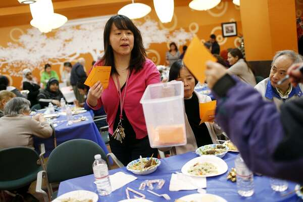 Rachel Chen collects ballots from residents during the year-end cooking contest at the 201 Turk St. apartment building, Thursday, December 19, 2013 in San Francisco, Calif.