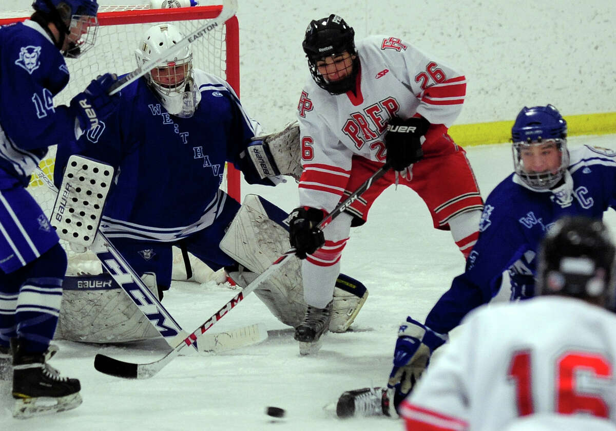 Fairfield Prep's Matt MCKinney looks to intercept the pass at the goal, during boys hockey action against West Haven at the Wonderland of Ice in Bridgeport, Conn. on Thursday January 9, 2014. Ready to block is West Haven goalie Michael Savino.