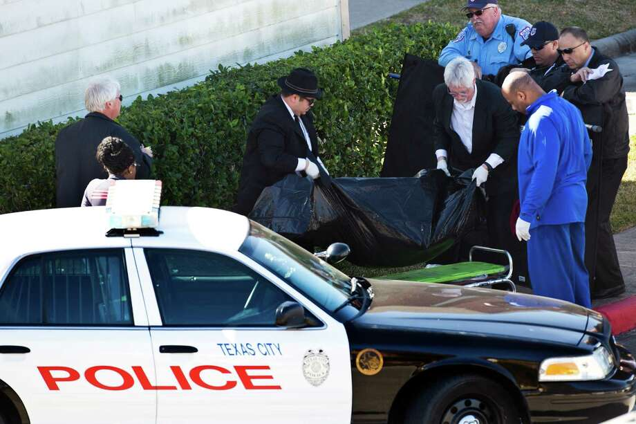Officials in Texas City remove the body of a murder suspect who, after hours of negotiation with authorities,  refused to leave his apartment. When officers raided the house, they found him hanging in a closet. Photo: Marie D. De Jesus, Staff / © 2014 Houston Chronicle