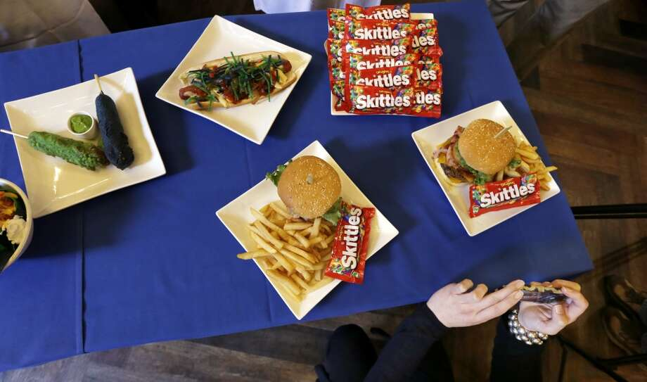 "New Seahawks team-themed menu items are displayed for media in a restaurant at CenturyLink Field.Clockwise from top-left: ""Boom"" Battered Corn Dogs, DangeRuss Dog, a bunch of Skittles, the Beast Burger and another Beast Burger. Photo: Elaine Thompson, Associated Press"