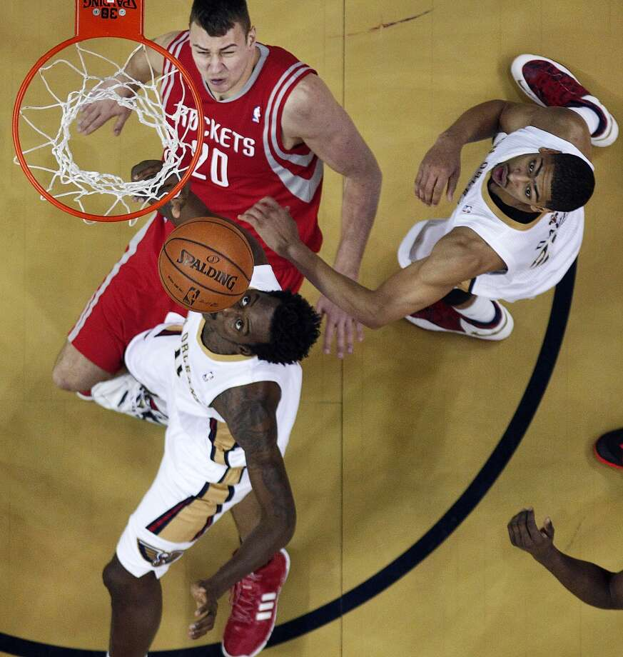 Rockets power forward Donatas Motiejunas (20) falls to the court as Pelicans small forward Al-Farouq Aminu, below, drives to the basket. Photo: Gerald Herbert, Associated Press