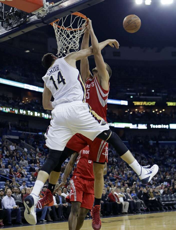 Pelicans center Jason Smith (14) blocks an attempted slam dunk by Rockets small forward Chandler Parsons. Photo: Gerald Herbert, Associated Press