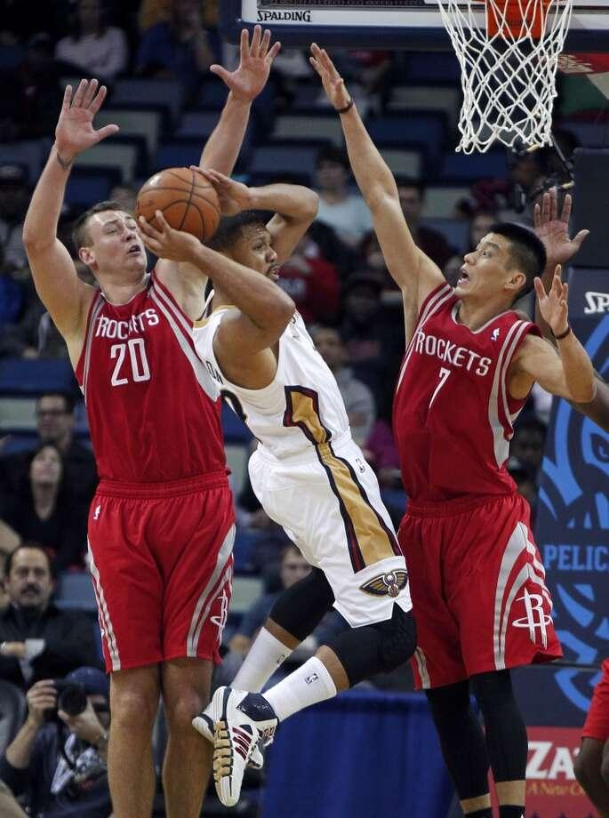Pelicans shooting guard Eric Gordon (10) tries to pass around Rockets power forward Donatas Motiejunas. Photo: Gerald Herbert, Associated Press