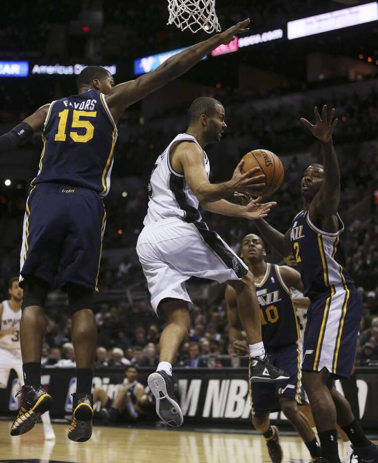 San Antonio Spurs' Tony Parker passes around Utah Jazz' Derrick Favors and Marvin Williams during the first half at the AT&T Center, Wednesday, Jan. 15, 2014. Photo: San Antonio Express-News