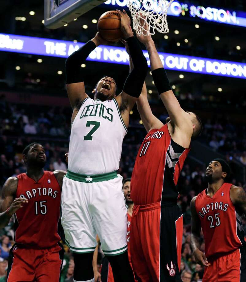 Boston Celtics forward Jared Sullinger muscles the ball to the basket against Toronto Raptors center Jonas Valanciunas, right, during an NBA basketball game in Boston, Wednesday, Jan. 15, 2014. Sullinger scored 25 points and grabbed a career-best 20 rebounds as theCeltics held on to snap a nine-game losing streak with an 88-83 victory. (AP Photo/Charles Krupa) ORG XMIT: MACK110 Photo: Charles Krupa / AP