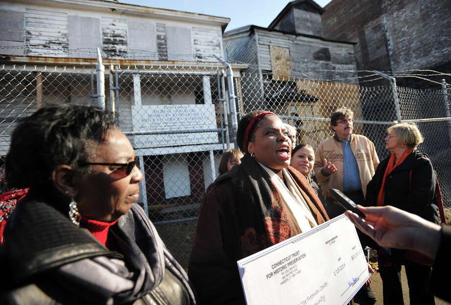 Maisa Tisdale, president/CEO of The Mary & Eliza Freeman Center for History and Community, holds a 20 thousand dollar check from the Connecticut Trust for Historic Preservation during a ceremony outside the Mary and Eliza Freeman houses, the oldest dwellings in Connecticut constructed by African Americans, on Main Street in BRidgeport's South End on Wednesday, January 15, 2014. Photo: Brian A. Pounds / Connecticut Post
