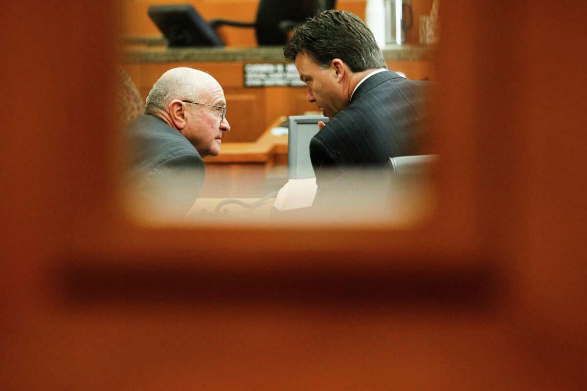 Dave Wilson, left, confers with his attorney during Wednesday's court hearing that ended with a ruling in his favor.