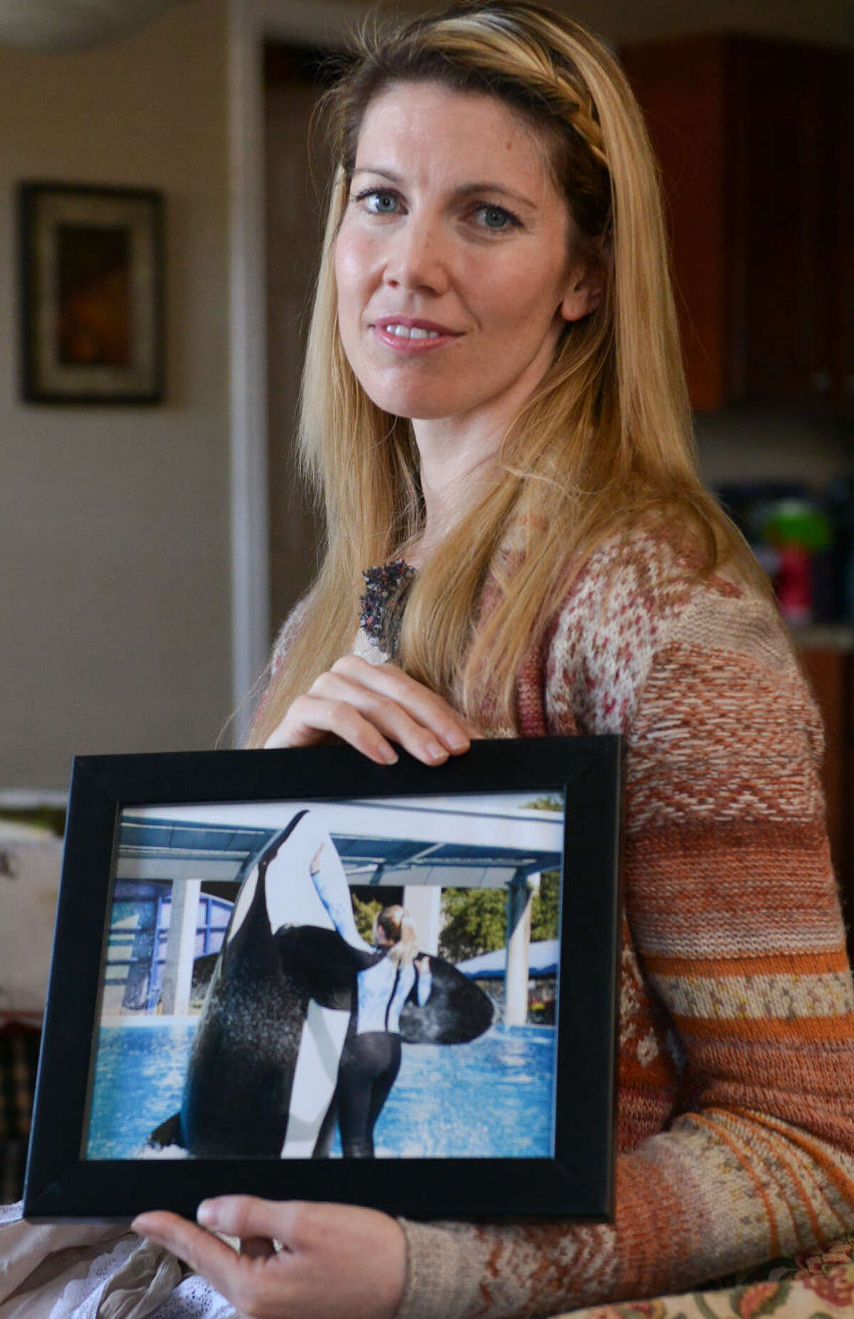 Bridgette Pirtle, who was employed at SeaWorld San Antonio from 2001 to '11, holds a picture of herself at work. She says