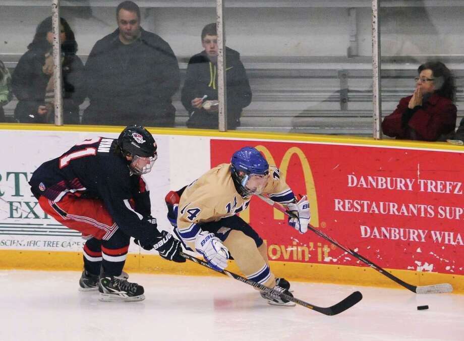 New Fairfield/Immaculate's Jake Ryan, left, battles Newtown's Jonathan Lovorn for the puck in the high school hockey game between Newtown and New Fairfield/Immaculate at Danbury Arena in Danbury, Conn. on Wednesday, Jan. 15, 2014. Photo: Tyler Sizemore / The News-Times
