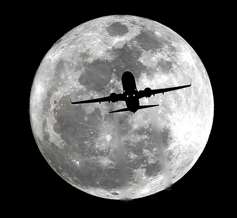 Silhouetted by a 'wolf moon' - the January full moon - an airplane makes its final approach to Los Angeles 
