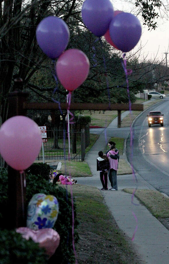 Monica Bloompott visits an area with her children Thursday January 16, 2014 where Tatyana Babineaux, 9, was killed yesterday on the 11,700 block of Braesview after being hit by a truck. Babineaux was walking to Larkspur Elementary about 7:00 am. when she was struck by the hit-and-run driver. Photo: John Davenport / ©San Antonio Express-News/Photo may be sold to the public