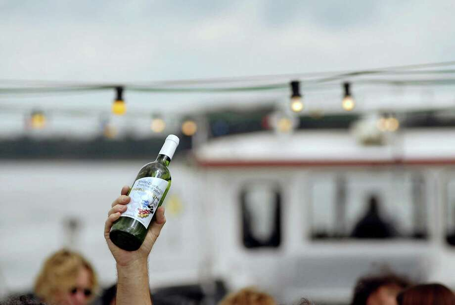 "A man holds a bottle of the first special French-German wine in 2008 on a boat, the Weinland Baden, in the middle of the Rhine River near Breisach, Germany. An Alsacian and German winegrower created the wine called ""Vin des deux rives"" in French (Wine of the two riverbanks) or ""Zweilander Wein"" (Two lands wine) in German as part of the local newspaper ""L'Alsace."" Photo: SEBASTIEN BOZON, Getty Images / 2008 AFP"