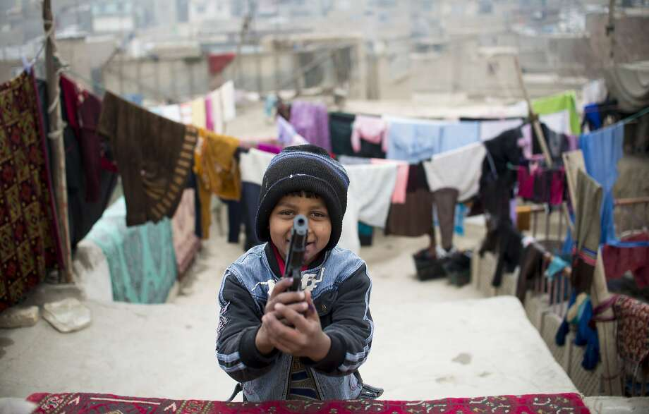 You shoot me, I shoot you:Nine-year-old Zubair Ahmad points a plastic gun at a photographer on a rooftop in the 