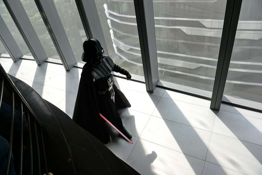 TOPSHOTS A staff member dressed as the Darth Vader (C) character from George Lucas' Star Wars films arrives for photographers at the opening of Disney's Lucasfilms' new animation production facility, the Sandcrawler in Singapore on January 16, 2014. The award-winning Sandcrawler building was officially opened on January 16, as its regional headquarters for Lucasfilm Singapore. AFP PHOTO/ ROSLAN RAHMANROSLAN RAHMAN/AFP/Getty Images Photo: Roslan Rahman, AFP/Getty Images