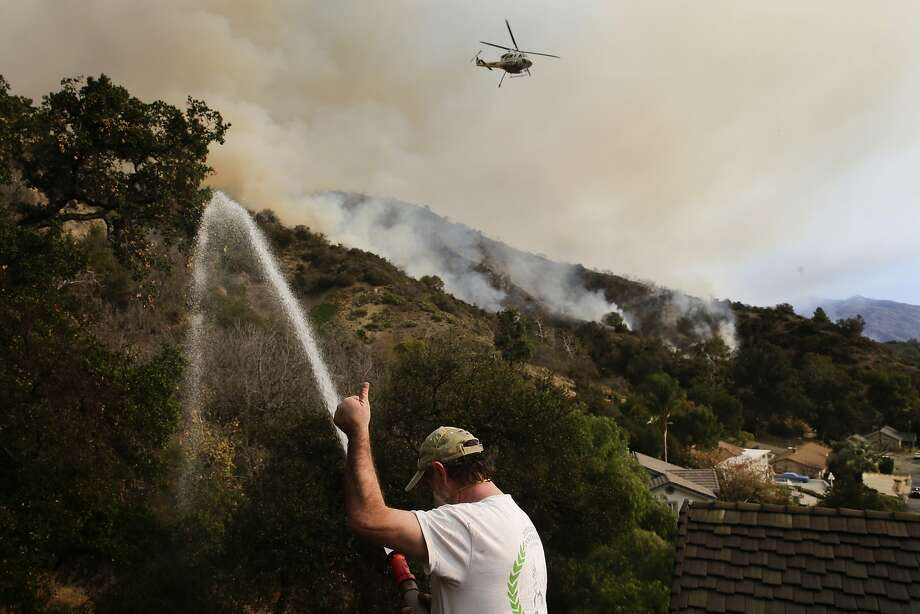 Mark Davis gives a thumbs-up to a firefighting helicopter overhead as he sprays down his property in Azusa to protect it from an out-of-control wildfire in the dry foothills of the San Gabriel Mountains. Photo: Jae C. Hong, Associated Press