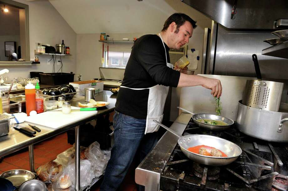 Rob Atkinson, owner of Mima's Meatballs & More on Mill Plain Road in Danbury, Conn., prepares Italian Wedding Soup for a customer Thursday, January 16, 2014. Photo: Carol Kaliff / The News-Times