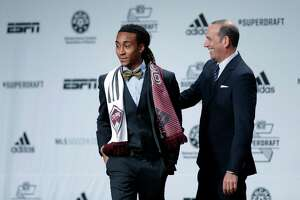 Marlon Hairston, left, accompanied by MLS Commissioner Don Garber walks on stage after being selected by Colorado Rapids in the first round of the 2014 Major League Soccer SuperDraft, Thursday, Jan. 16, 2014, in Philadelphia. (AP Photo/Matt Rourke)