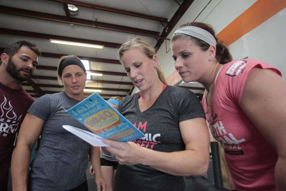 (l-r) Daniel Ward, Janet Black, Beth Spearman and Jamie Carter all read a good luck card from a member of Atomic CrossFit family Wednesday, July 17, 2013 at Atomic CrossFit in Stafford,Texas. The group are all part  of a six member team training for the Crossfit Games in Carson California that begin July 24. The team is comprised of 3 men and 3 women Beth Spearman Janet Black Jamie Carter Daniel Ward Will Maloy Ben Bacon  Wednesday, July 17, 2013, in Stafford. ( Billy Smith II / Chronicle ) Photo: Billy Smith II, Chronicle