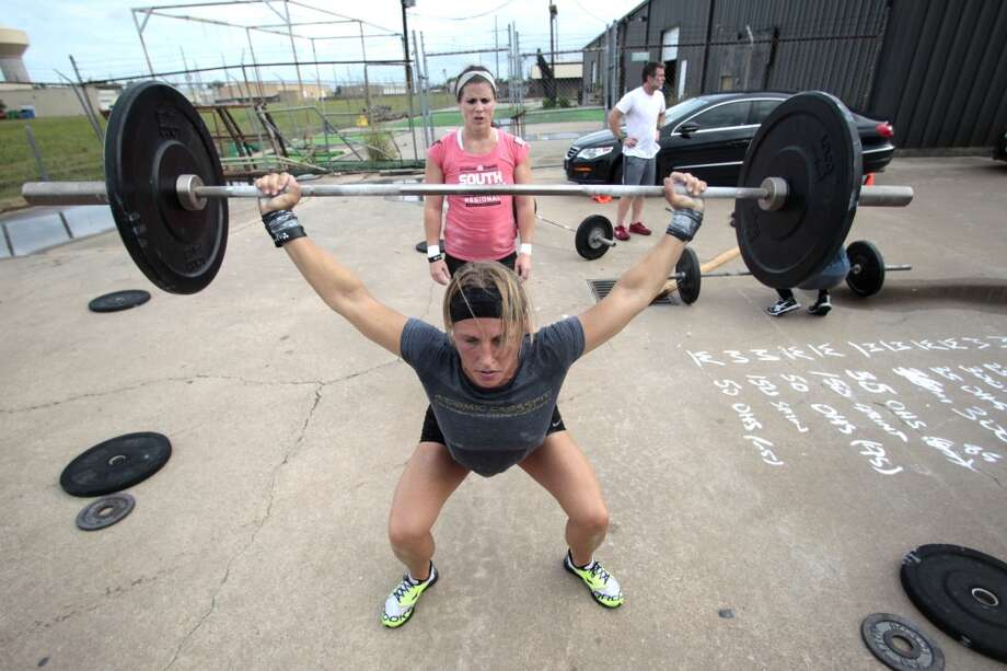 (front-back) Janet Black completes a overhead squat as Jamie Carter supports her at Atomic CrossFit in Stafford,Texas, Wednesday, July 17, 2013. Black and Carter are part of a team of six members training for the Crossfit Games in Carson California that begin July 24. The team is comprised of 3 men and 3 women Beth Spearman, Janet Black, Jamie Carter, Daniel Ward ,Will Maloy, and Benjamin Bacon. ( Billy Smith II / Chronicle ) Photo: Billy Smith II, Chronicle